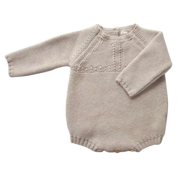 Knitted babygrow made with 100% cotton in a soft beige colour. Wooden buttons fastening at the back and bottom end. Traditional stitches details around the front, neck and cuffs. Soft, comfortable and stretchy allows for maximum comfort for the little ones. Combine with a crisp white collar shirt underneath to add layers and matching Blanca Bonnet to keep warm on the colder days. FRONT