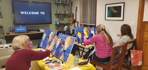 People painting together watching tutorial on one big screen