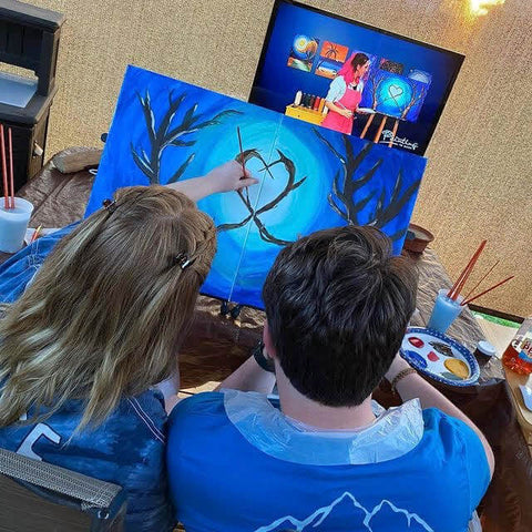 Couple painting together on a diptych acrylic painting