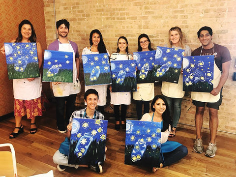 Participants holding up their paintings after a painting teambuilding activity