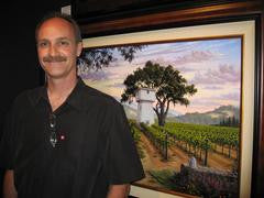 Napa Valley Wine Country Artist Patrick O'Rourke at Gallery 1870 in Yountville standing in front of his painting Sunset at Silver Oak.
