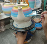 Painting rainbow teapot by hand