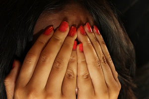 Woman's hands covering her face