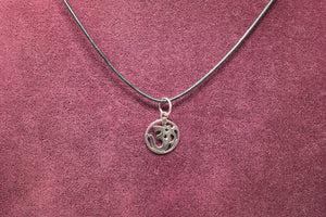 Sterliing Silver OM pendant on maroon background