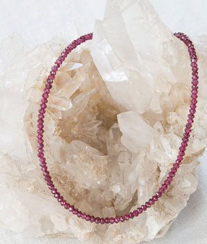 Garnet Necklace draped over Quartz Crystal