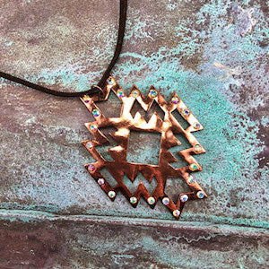 Native pattern copper necklace with iridescent rhinestone bling on a brown faux leather strand.