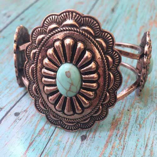 Copper magnolia concho western cuff with turquoise accent.