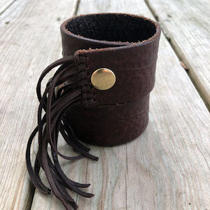 Western tooled leather cuff in brown with fringe.