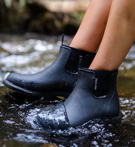 Person wearing Black Bobbi Gumboots by Merry People standing in water