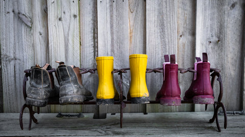 Bobbi Gumboots by Merry People sitting on a shoe rack.