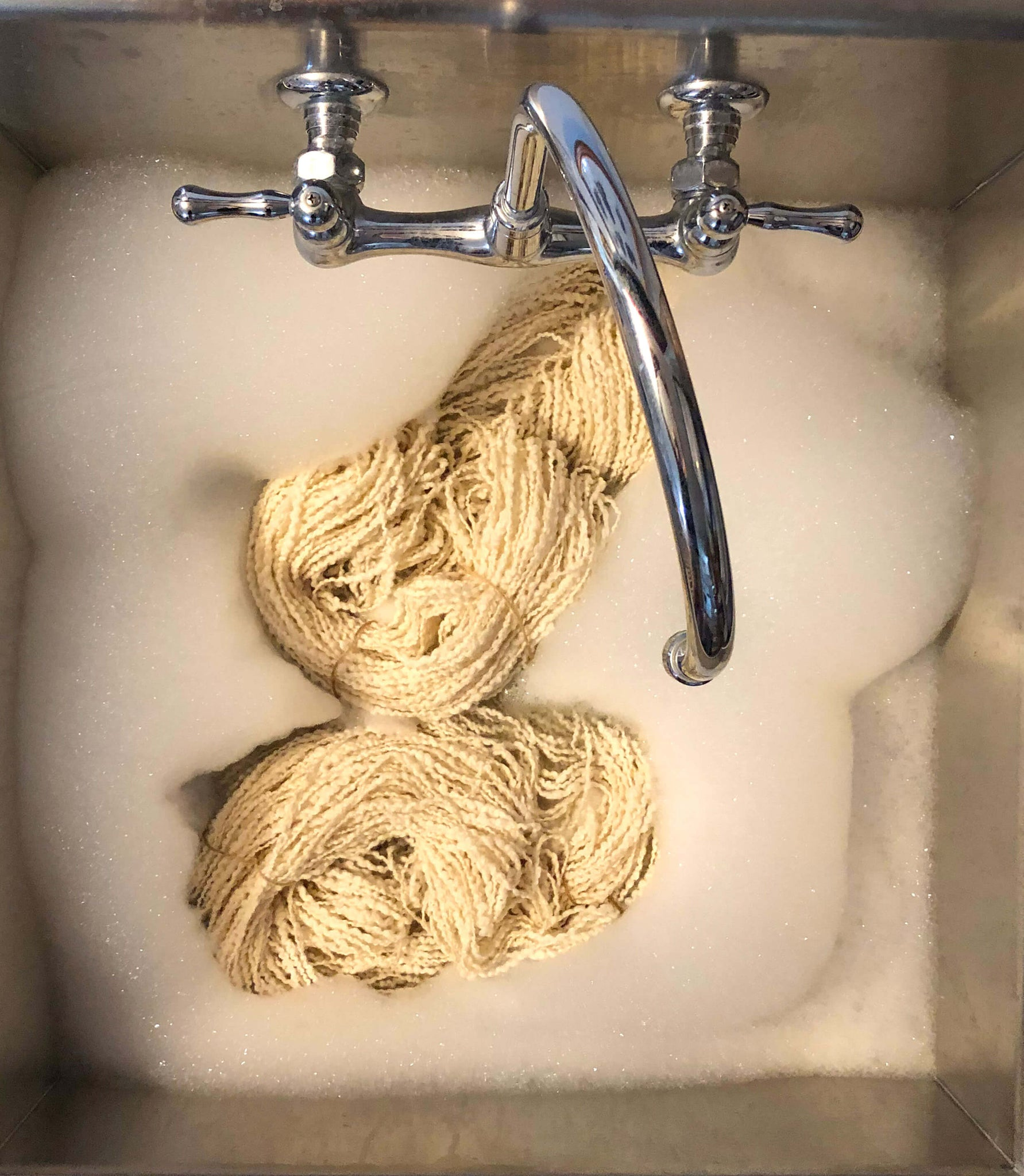 Scouring wool in a sink