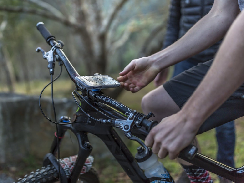 mountain biker using quad lock iphone mount and poncho