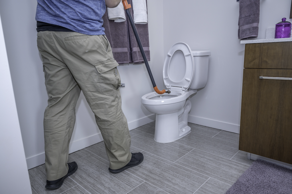 how to plunge a toilet: Man using an auger on a toilet
