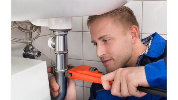 How to use a drain snake: Plumber with tools