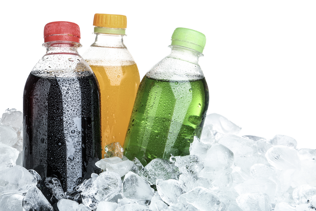 Bottles of soda surrounded by ice cubes