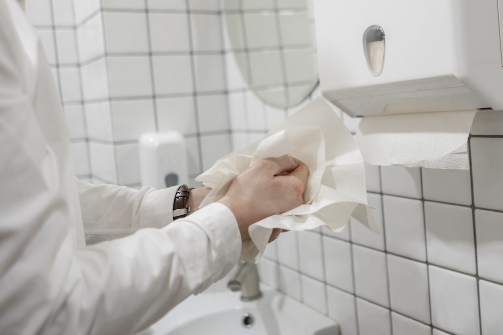 toilet won't unclog: man wiping his hand with a tissue