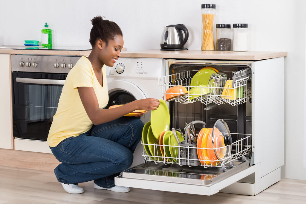 Woman arranging dishes in a dishwasher