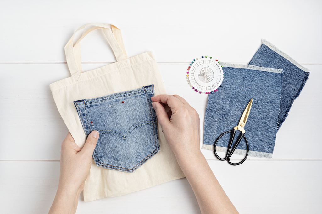 woman creating a bag out of recycled jeans