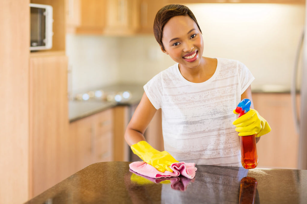 Happy woman wiping the kitchen counter