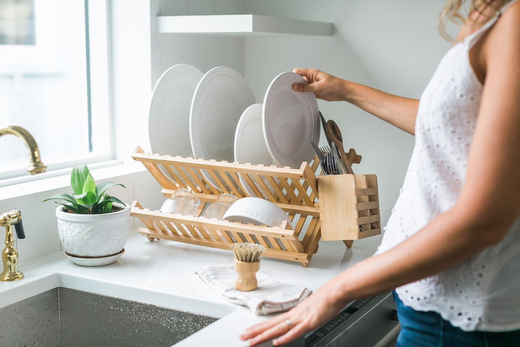 Eco friendly kitchen: woman putting plates on a bamboo dish rack