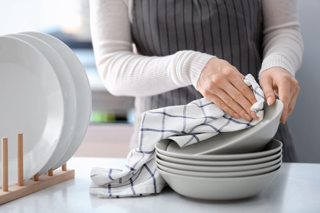 Woman wiping bowls with a dish cloth