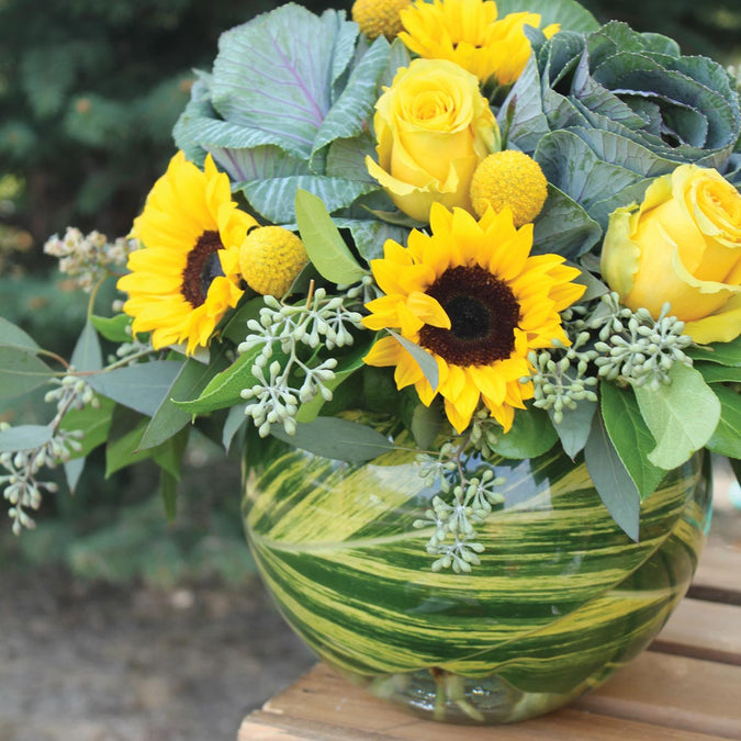 small bubble ball used as a vase with sunflowers yellow roses and ornamental cabbage