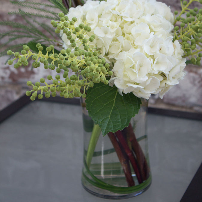 gathering vase in use with hydrangeas on a glass patio table