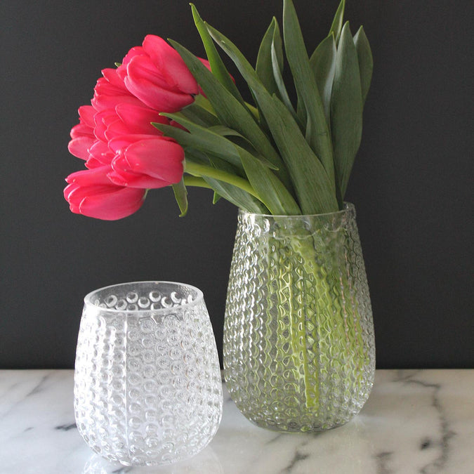 small pebble stone vase and medium pebble stone vase filled with red tulips
