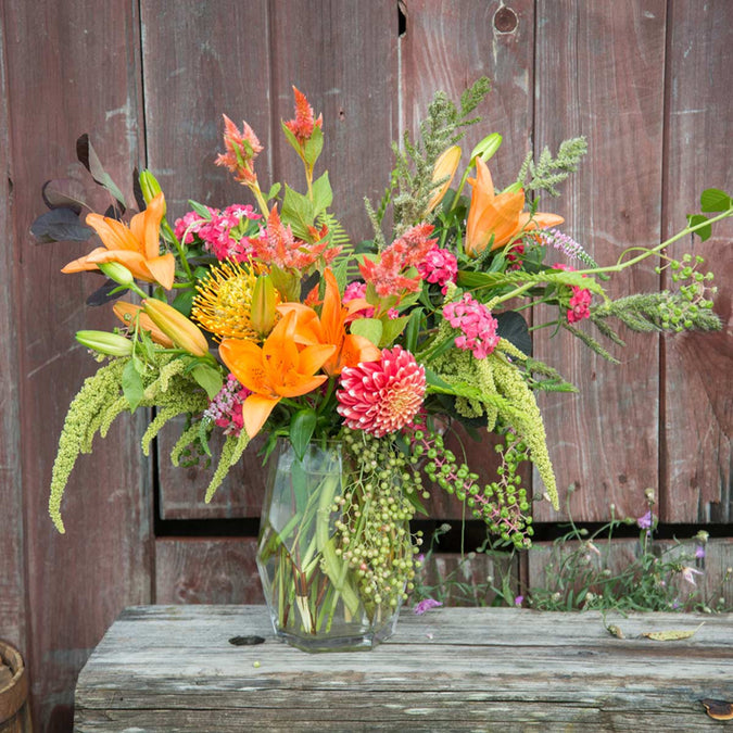 large prism vase filled with orange and pink flowers