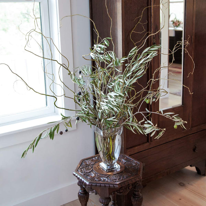 large regal vase filled with olive branches and curly willow