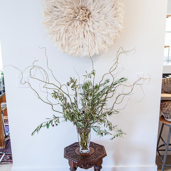 large regal vase filled with olive branches and curly willow on end table