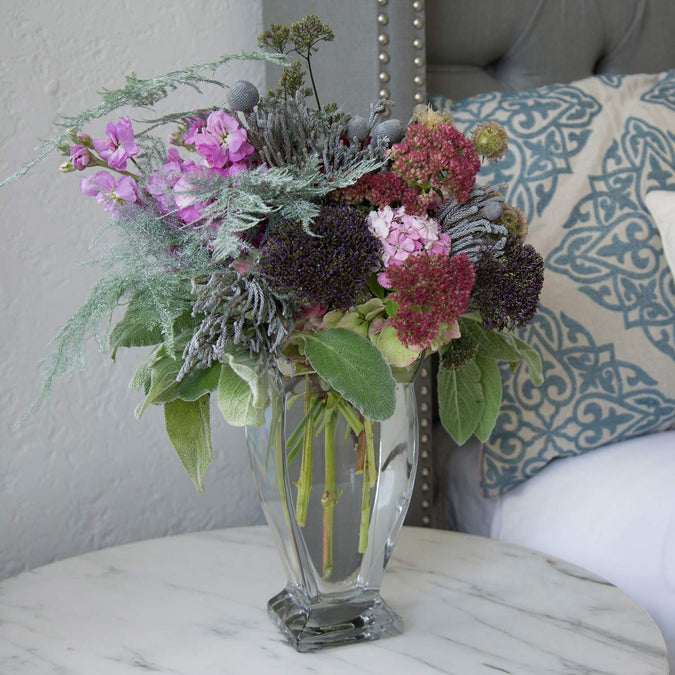 small regal vase filled with flowers on a nightstand