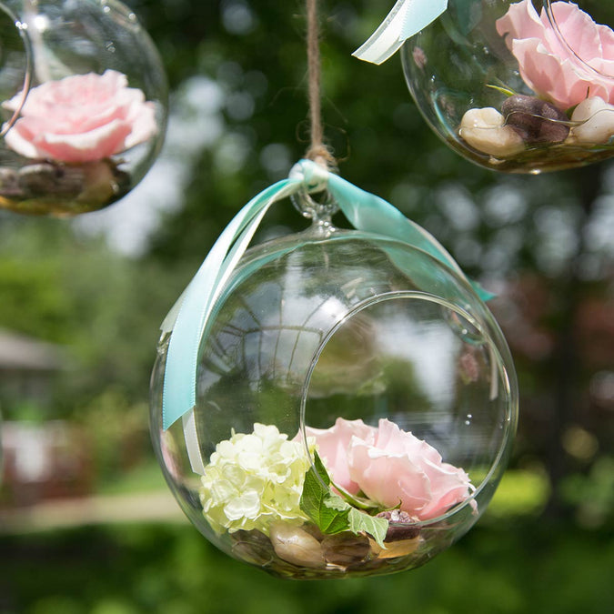 medium round hanging terrarium filled with flowers and stones hanging outside