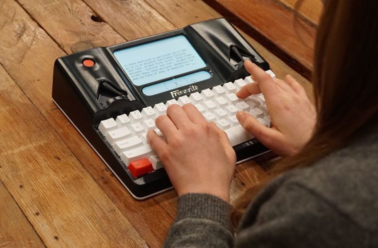 writer typing on wood surface portable