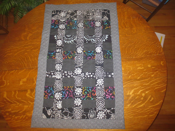 Black batik and calico quilted insulated table runner with a splash of color