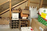 Wine bottles stacked in boxes under the stairs