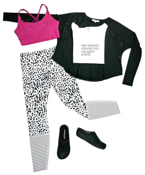 Image of Walking Cradles Clogs styled with atheleisure clothing items which include black and white tights, a bright pink sports bra, a graphic t-shirt and a loose, long sleeve top.