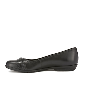 Side image of the Flynn. A comfortable black leather slip on shoe with a low heel and a small buckle detail on the toe.  Available in narrow width, wide width and extra wide widths.