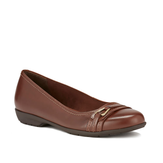 Image of the Flynn. A comfortable brown leather slip on shoe with a low heel and a small buckle detail on the toe.  Available in narrow width, wide width and extra wide widths.