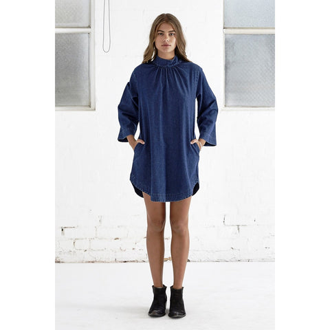 A 70's inspired smock dress with key seasonal high neck detail. In soft washed lightweight denim and featuring invisible back zip closure and hidden side pockets