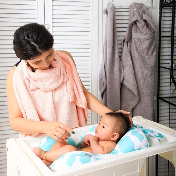 Mum bathing baby using Minene bath buddy - floating bath support for baby bath