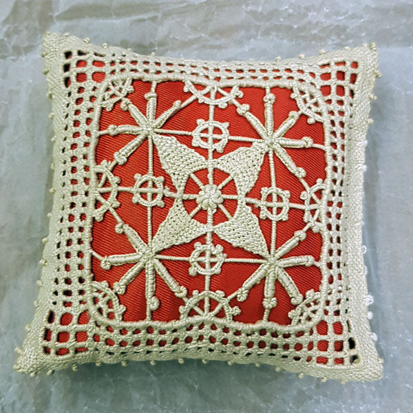 A Ruskin Lacework pin cushion from Armitt House
