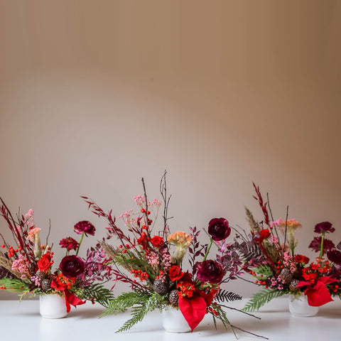 Trio of Festive Red Holiday Arrangements in White Vases