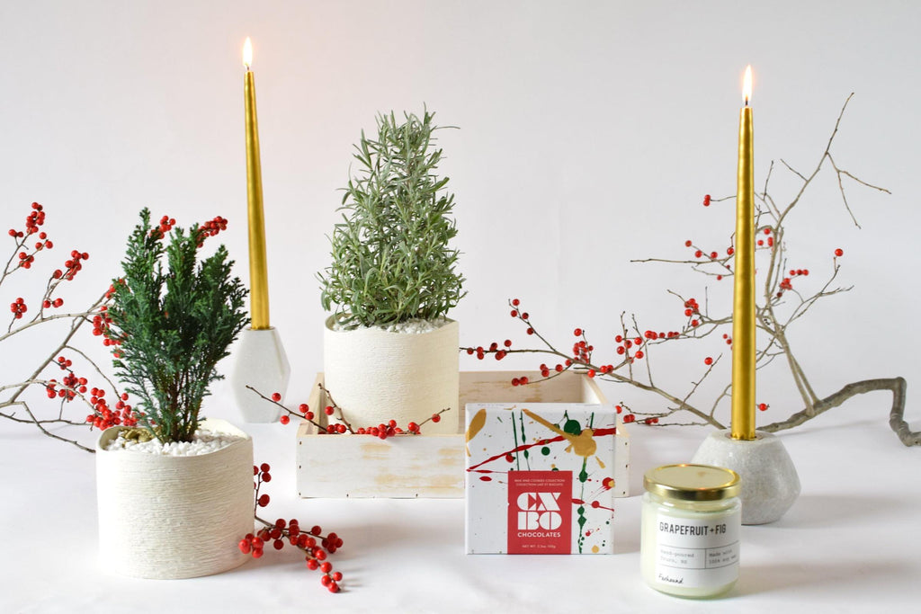 Holly Jolly bundle: two potted trees, two marble candle holders with tall gold tapered candles, soy candle and box of CXBO Festive Chocolates