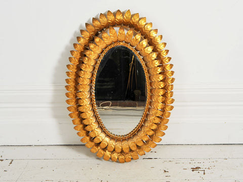 A 1950's French oval mirror with double layer of surrounding gold metal leaves