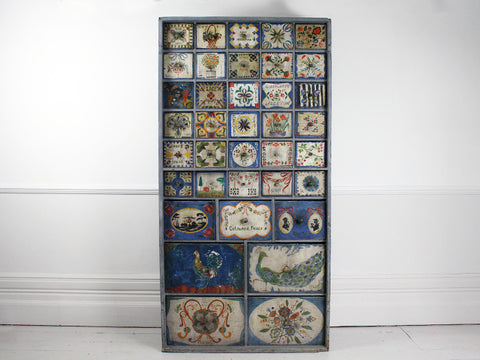 A 19th century haberdashery cupboard with 37 unique hand painted drawers