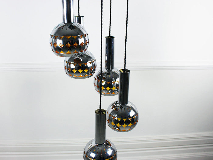 A 1960's 5 headed steel ceiling light with amber lining