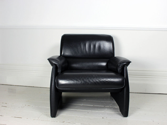 A pair of vintage black leather De Sede armchairs