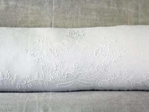 An antique linen bolster with embroidered pair of birds by Charlotte Casadéjus