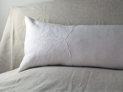 An antique linen bolster with scalloped Cornely embroidery by Charlotte Casadéjus